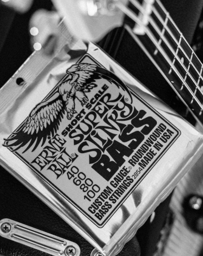 Packet of Ernie Ball Slinky strings on-top of an amp, next to a bass.